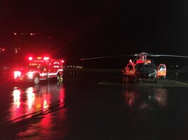 An MH-60T Jayhawk helicopter crew stationed at Air Station Kodiak transfers an injured 6-year-old girl to Kodiak Fire Department emergency medical service personnel waiting at the Kodiak (Alaska) Airport July 16, 2019.
