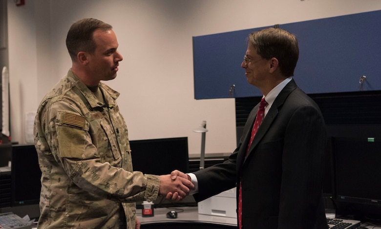 Lt. Col. Stephen Toth, 2nd Space Operations Squadron commander, left, presents a coin to Johnathon Caldwell, Lockheed Martin Space vice president of navigation systems, for their support of the space mission at Schriever Air Force Base, Colorado, July 29, 2019. Schriever AFB solely operates the GPS constellation of over 30 satellites which provides worldwide precision, navigation, and timing services to approximately 4 billion users. (U.S. Air Force photo by Airman 1st Class Jonathan Whitely)
