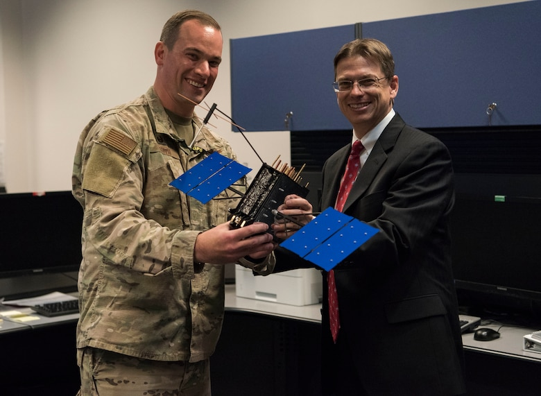Johnathon Caldwell, Lockheed Martin Space vice president of navigation systems, right, presents Lt. Col. Stephen Toth, 2nd Space Operations Squadron commander, with a GPS III model satellite as a token of appreciation for the 2nd SOPS critical mission in space at Schriever Air Force Base, Colorado, July 29, 2019. The 2nd SOPS operates the largest Department of Defense spacecraft constellation using the Master Control Station and a worldwide network of monitor stations and ground antennas. (U.S. Air Force photo by Airman 1st Class Jonathan Whitely)