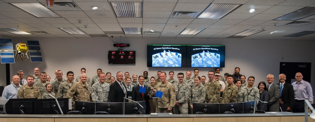 The 2nd Space Operations Squadron receives a GPS III model satellite from Lockheed Martin Space representatives at Schriever Air Force Base, Colorado, July 29, 2019. GPS has been identified by the Department of Homeland Security as essential to 14 of 16 industries that are classified as part of the Nations' critical infrastructure. (U.S. Air Force photo by Airman 1st Class Jonathan Whitely)