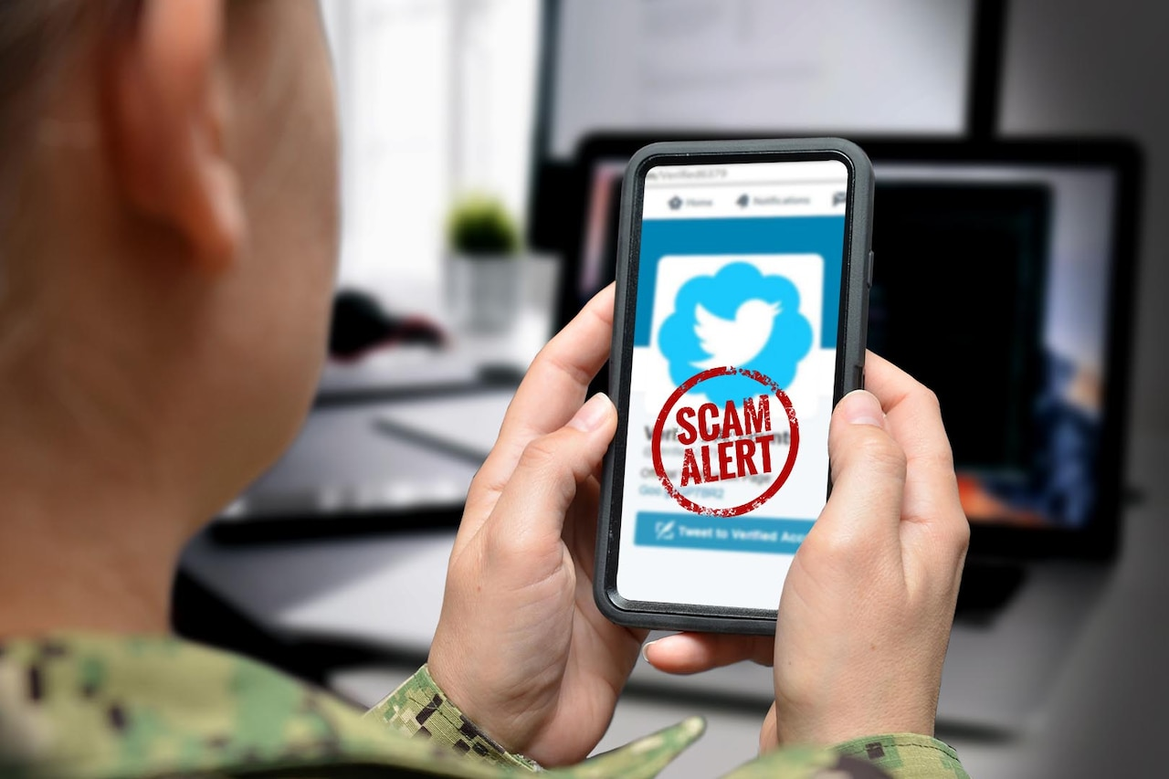 "A Navy sailor holds up a smartphone, making visible a screen that shows a red circle with the words ""scam alert"" in it across a webpage that looks like a social media site."