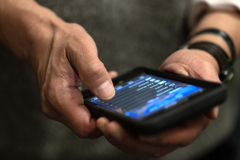 A man's hands typing on a cellphone. The contents on the screen are undeterminable.