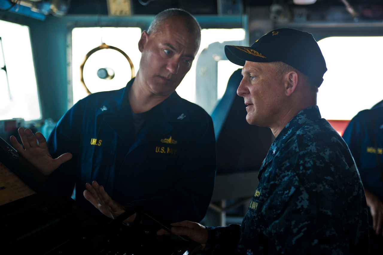 Two Navy officers talk.