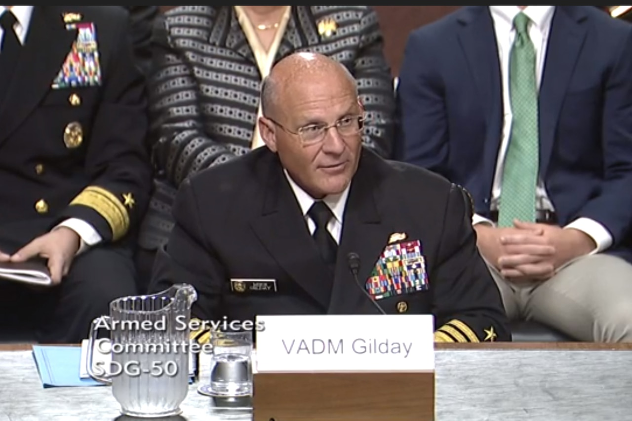 A Naval officer speaks while seated at a table..