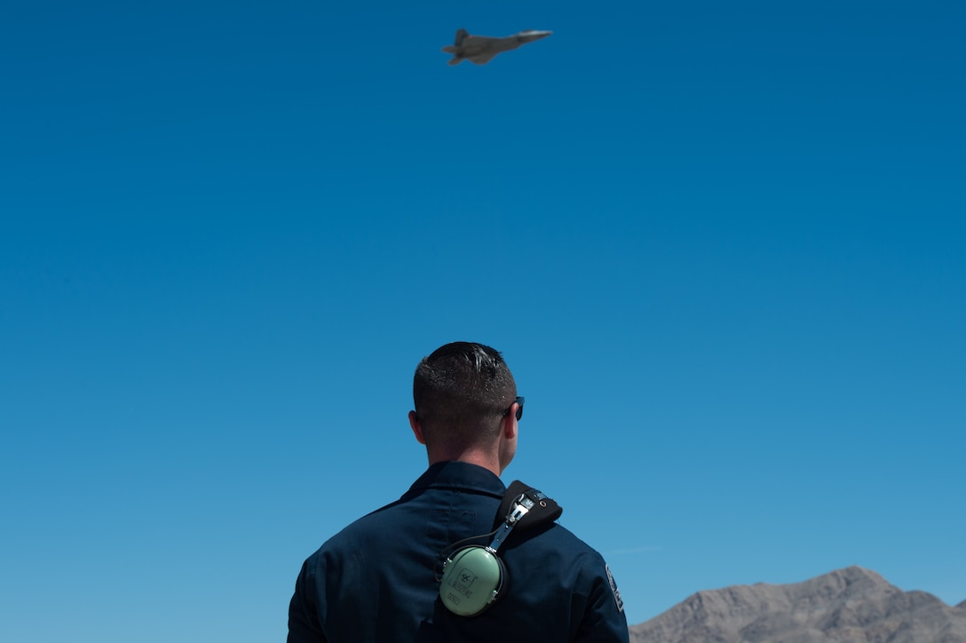 U.S. Air Force Staff Sgt. Lenny Buscemi, 94th Aircraft Maintenance Unit dedicated crew chief, watches an F-22 Raptor after takeoff at Nellis Air Force Base, Nevada, July 18, 2019.