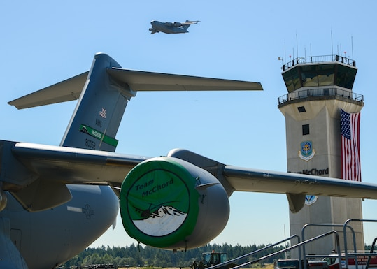 The C-17 West Coast Demo Team flies above the first C-17 Globemaster III delivered to McChord Field during a rededication ceremony celebrating the 20th anniversary of C-17 Globemaster IIIs at McChord Field, July 26, 2019, at Joint Base Lewis-McChord, Wash. The first C-17 is still operational and flying missions out of McChord Field. (U.S. Air Force photo by Staff Sgt. Joshua Smoot)