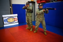 IMAGE: 190613-N-PO203-0122 CHESAPEAKE, Virginia (Jun. 13, 2019) Sailors assigned to the Center for Security Forces detachment in Chesapeake, Va., demonstrate the Office of Naval Research Global (ONRG) TechSolutions-sponsored Tactically Reconfigurable Artificial Combat Enhanced Reality (TRACER) system. TechSolutions partnered with Naval Surface Warfare Center Dahlgren Division to develop the TRACER package, which consists of a virtual-reality headset, a backpack, a state-of-the-art simulated weapon designed to deliver realistic recoil, and a software package that creates multiple and adaptable simulation scenarios for security personnel to experience. ONRG TechSolutions allows Sailors and Marines to submit technology requests directly to the development community for rapid response prototyping. (U.S. Navy photo by John F. Williams)