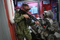 IMAGE: 190613-N-PO203-0232 CHESAPEAKE, Virginia (Jun. 13, 2019) A Sailor assigned to the Center for Security Forces detachment in Chesapeake, Va., demonstrate the Office of Naval Research Global (ONRG) TechSolutions-sponsored Tactically Reconfigurable Artificial Combat Enhanced Reality (TRACER) system. TechSolutions partnered with Naval Surface Warfare Center Dahlgren Division to develop the TRACER package, which consists of a virtual-reality headset, a backpack, a state-of-the-art simulated weapon designed to deliver realistic recoil, and a software package that creates multiple and adaptable simulation scenarios for security personnel to experience. ONRG TechSolutions allows Sailors and Marines to submit technology requests directly to the development community for rapid response prototyping. (U.S. Navy photo by John F. Williams)