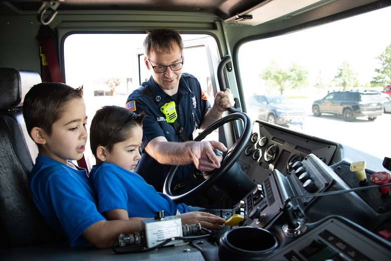 Alex, 9, left, and Lucas, 5, learn about the control panel of fire truck with Steve Leibensperger, 50th Civil Engineer Squadron firefighter, during the back-to-school event at Schriever Air Force Base, July 30, 2019. During the event, kids were able to get backpacks filled with back-to-school gear and also view a weapons demonstration, a patrol car static display, a school bus static display, a fire truck display, and a USAFA falconry demonstration. (U.S. Air Force photo by 2nd Lt. Idalí Beltré Acevedo)