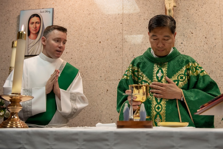 2nd. Lt. Tyler Harris, Air Force Reserve Command chaplain candidate out of Robins Air Force Base, Georgia, assists Capt. Antonio Rigonan, 374th Airlift Wing chaplain, with Catholic Mass at Yokota Air Base, Japan, July 2, 2019.