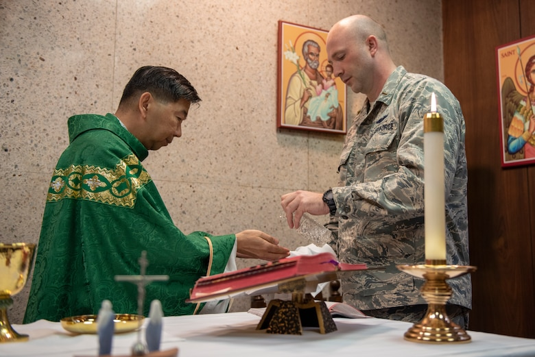 2nd. Lt. Madison Hayes, Air Force Reserve Command chaplain candidate out of Robins Air Force Base, Georgia, assists Capt. Antonio Rigonan, 374th Airlift Wing chaplain, with Catholic Mass at Yokota Air Base, Japan, July 2, 2019.