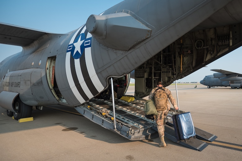 Master Sgt. Phil Speck, Public Affairs superintendent for the 123rd Airlift Wing, boards a C-130 Hercules aircraft at the Kentucky Air National Guard Base in Louisville, Ky., June 1, 2019, en route to France. Speck and 30 other Kentucky Air Guardsmen will participate in the 75th-anniversary reenactment of D-Day there. Two Kentucky C-130s will airdrop U.S. Army paratroopers over Normandy on June 9 as part of the commemoration. The aircraft has been striped with historically accurate Allied Forces livery in honor of the event, which turned the tide of World War II in the European theater. (U.S. Air National Guard photo by Dale Greer)