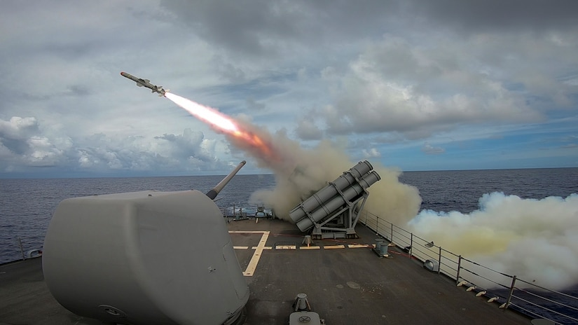A missile launches off the deck of a military vessel.