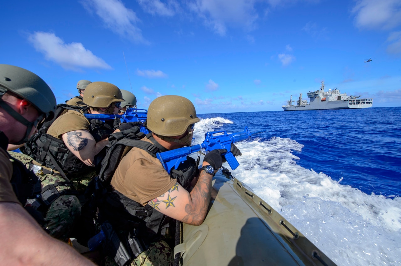 Armed military personnel in a small boat approach a larger military vessel.