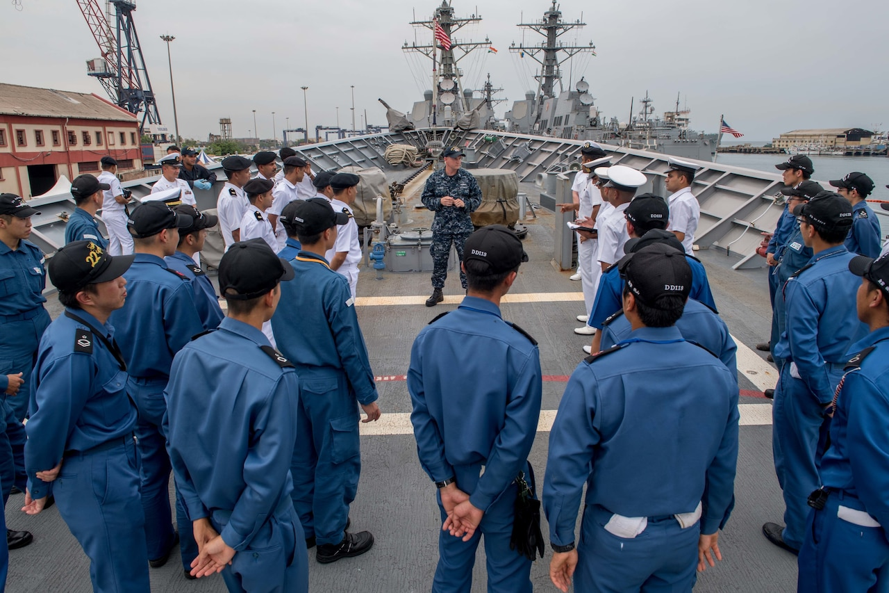 Military personnel gather around a U.S. sailor on the deck of a military vessel.