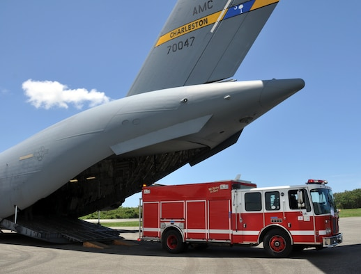 An aircrew from Joint Base Charleston, S.C., offloads a fire truck, along with an ambulance and firefighting equipment, from a C-17 Globemaster III aircraft during a humanitarian and training mission to the Dominican Republic, May 31, 2019. The equipment was donated by a fire department in Rochester, New York and transported under the Denton Cargo Program, which allows for humanitarian aid and supplies to be transported on military aircraft on a space-available basis. (U.S. Air Force photo by Capt. Justin Clark)