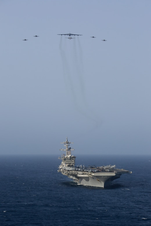 A photo of B-52 and Abraham Lincoln Carrier Strike Group.
