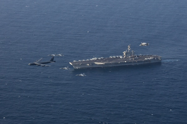 A photo of Abraham Lincoln Carrier Strike Group and a B-52.