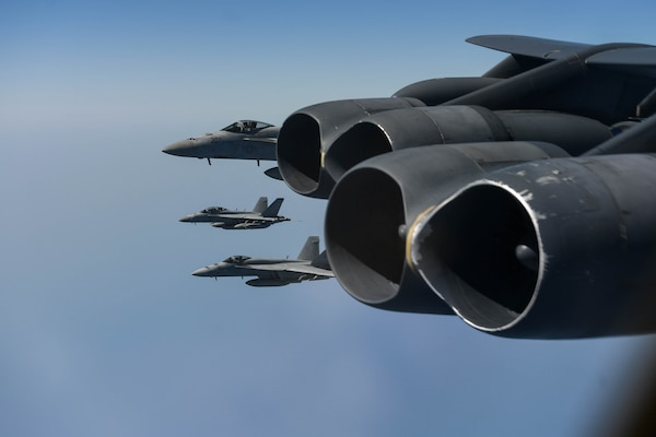 A photo of F-18 Hornets flying next to a B-52 Stratofortress.
