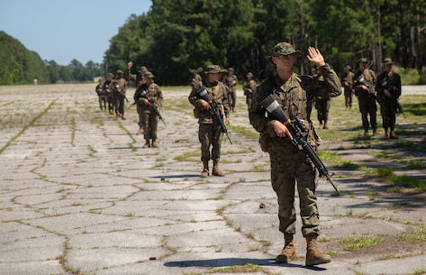U.S. Marine Corps recruits with Mike Company, 3rd Recruit Training Batallion, practice various hand-and-arm signals on a simulated patrol during Basic Warrior Training at Paige Field on Parris Island, S.C., May 15, 2019. BWT is a week-long training event that teaches recruits the basics of combat survival and advanced rifle manuevers. (U.S. Marine Corps photo by Cpl. Daniel O'Sullivan)