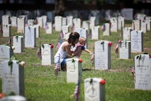 A local mother and her child put a single rose on the grave of a service member during the City of Beaufort's Annual Memorial Day Parade and remembrance ceremony May 27, 2019 at Beaufort National Cemetery in Beaufort, S.C. The Tri-Command and local community held the parade to remember and honor the men and women who have served and died in the service of the nation in the U.S. Armed Forces. (U.S. Marine Corps photo by Lance Cpl. Christopher McMurry)
