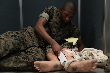 A U.S. Marine Corps Recruit with Mike Company, 3rd Recruit Training Battalion, performs combat casualty care on the final practical application aboard Marine Corps Recruit Depot Parris Island, S.C., May 28, 2019. Within the course of recruit training, recruits learn how to conduct combat casualty care, troop formations, casualty carries, as well as hand and arm signals. (U.S. Marine Corps photo by Cpl. Andrew Neumann/Released)