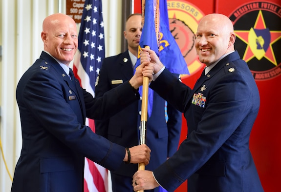 Col. Todd Tobergte, 926th Operations Group commander, passes the 26th Space Aggressor Squadron guidon to Lt. Col. Jeremy Nutz, incoming 26 SAS commander, during a ceremony June 1, 2019.