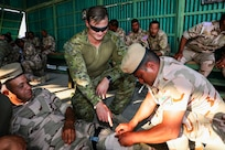 Australian Army lance corporal Brodie Bush from Task Group Taji 8, instructs an Iraqi soldier in the use of combat pressure gauze, on Camp Taji, Iraq, May 6, 2019. Combat Life Saver training builds soldier's confidence in providing lifesaving measures in potentially hostile situations. Combined Joint Task Force – Operation Inherent Resolve focuses on providing training, support, and equipment to enhance the professionalism, technical expertise and equipment capabilities of Iraqi Security Forces. This will enable the ISF to counter future external and internal threats independently and establish permanent security across the country. (Portions of this photo have been blurred to protect operational security).
