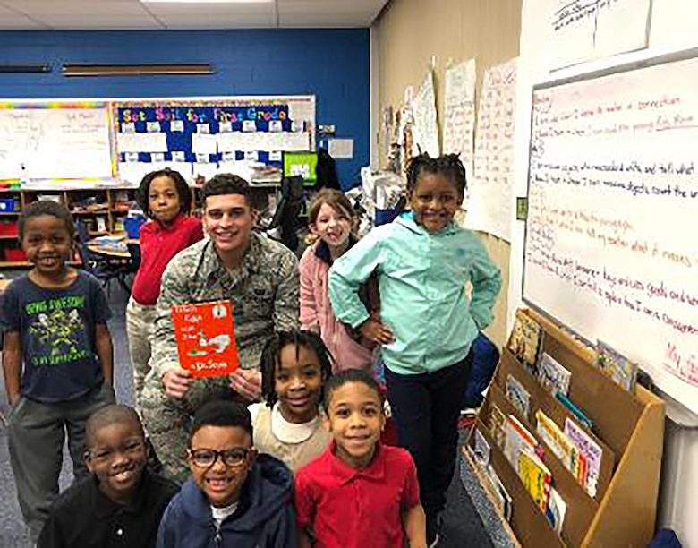 Airman 1st Class Kyle Valerio, assigned to the 718th Intelligence Squadron, serves as a mentor for young children at Bassette Elementary school, reading as a part of the Mayor's Book Club to promote interest in books and literacy.