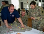Bryan Whitaker, Assistant Director, St. Clair County Emergency Management Agency, goes over a map outlining the levee systems of the Metro East Sanitation District and the Prairie Du Pont Levee District, covering the north and south sides of St. Clair County with Spec. Jacqueline Herrera, of Cicero, Illinois, and Sgt. Andrew Gray, of Warren, Illinois. Herrera and Gray are among the 10 Soldiers from 2nd Battalion, 123rd Field Artillery Regiment working flood duty in the East Carondelet, Illinois area.