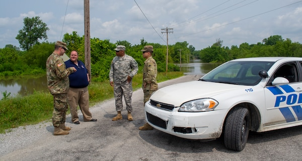 Sgt. Joey White, of Chicago, Pfc. Andrew Gusich, of Mendota, and Spec. Eder Castillo, of Rochelle, discuss levee patrol operations