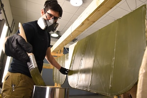 DAYTON, Ohio -- Museum restoration specialist Casey Simmons applies green dope to the Avro 504K control surfaces. This aircraft was originally built in 1966 by the Royal Canadian Air Force's Aircraft Maintenance & Development Unit. Preserving the Air Force's proud legacy, the Restoration Division restores aircraft and aerospace vehicles to historically accurate and visually striking levels. (U.S. Air Force photo by Ken LaRock)
