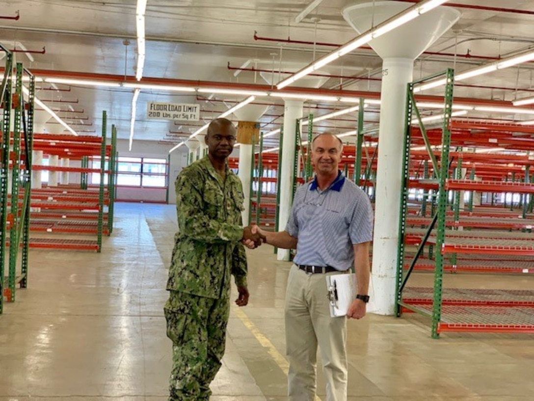 Terry Surdyke, an area manager for DLA Disposition Services' South-East region, and Navy Lt. Cmdr. Jay McFarland, operations officer at Jacksonville's Fleet Logistics Center, celebrate the clearing of Building 110.
