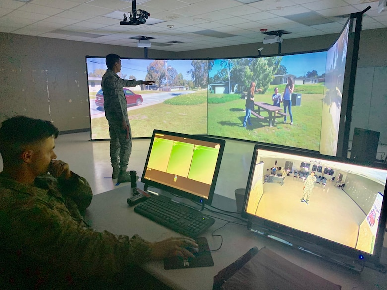 Airman 1st Class Valric Suyom, a recent graduate of the Security Forces apprentice course, participates in a use of force training scenario in the Multiple Interactive Learning Objectives (MILO) simulator as Staff Sgt. James McKinney, 343rd Training Squadron instructor, guides the training at Joint Base San Antonio-Lackland, Texas, May 29, 2019. The MILO system puts student in various interactive use of force training scenarios, including the potential application of deadly force, through the use of enhanced video screens.  (U.S. Air Force photo by Dan Hawkins)