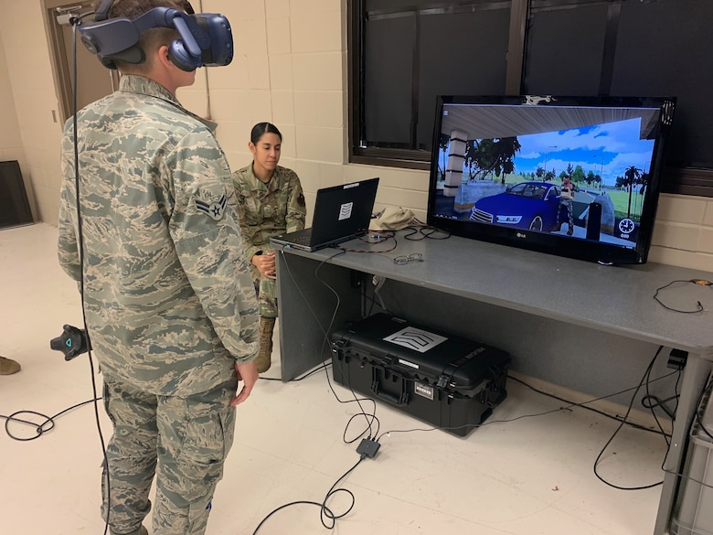 Airman 1st Class Taylor Waldron, a recent graduate of the Security Forces apprentice course, participates in a use of force training scenario in virtual reality environment simulator as Staff Sgt. Marcia Maldonado, 343rd Training Squadron instructor, facilitates training at Joint Base San Antonio-Lackland, Texas,May 29, 2019. The 343rd Training Squadron has added the VR training simulators as part of a beta-test in conjunction with a civilian vendor at no cost to the unit through a partnership with AFWERX.  (U.S. Air Force photo by Dan Hawkins)