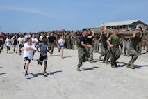 Students from Parkwood Elementary School run alongside Marines during a log run competition at a Commander's Cup event with 2nd Transportation Battalion, Combat Logistics Regiment 2, 2nd Marine Logistics Group at Onslow Beach, May 24, 2019. The unit adopted Parkwood Elementary in January 2019 School and are volunteering their time with students weekly. (U.S. Marine Corps photo by Cpl. Ashley Lawson)