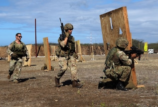 A U.S. Soldier coaches members of the 24th Commando Royal Engineers during weapons training.