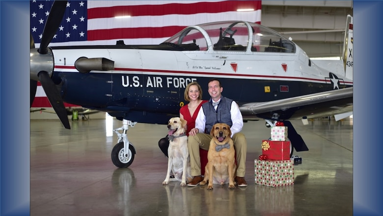 """Air Force Reserve Citizen Airman Maj. Hilary Foley, 96th Flying Training Squadron T-1 Jayhawk instructor pilot, Laughlin Air Force Base, Texas, poses for a holiday family portrait with her husband, 85th Flying Training Squadron Commander Lt. Col. Bryan Foley, and their yellow lab """"kids,"""" Weston and Chase. As a former active duty C-5 pilot, current Reserve instructor pilot and wife of an active duty squadron commander, Major Foley has the perfect experience and background to help """"bridge the gap"""" between active and Reserve teammates and families. (Courtesy photo)"""