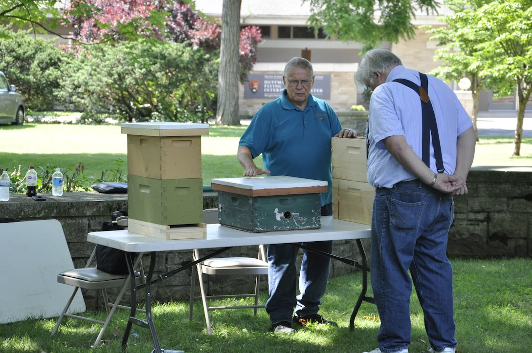 Dwight Wells, a sustainable beekeeper with the Propolis Project, LLC, explains the beekeeping process to an attendee at the 2018 Pollinator Expo. Attendees at this year's expo n June 19 can see a live beekeeping demonstration and learn how to beekeep. (U.S. Air Force photo/W. Eugene Barnett)