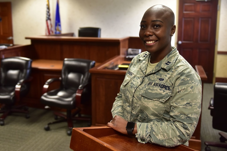 A woman wearing the Airman Battle Uniform stands in front of a judge seat.