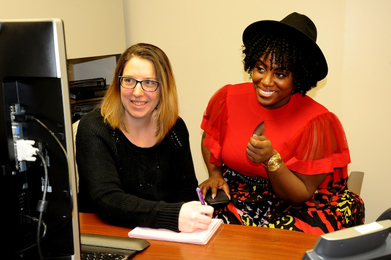 Sharonda Grandberry, Army veteran and contract specialist with the U.S. Army Engineering and Support Center, Huntsville, selected as the 2019 Face of Queen Size Magazine, an award-winning monthly print and digital publication dedicated to servicing the full-figured industry. Here, she discusses a proposed contract with co-worker, Jasmine Reason. (Photo by David San Miguel)