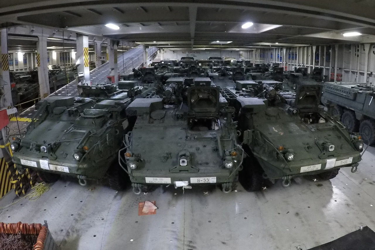 Armored vehicles sit in the hold of a ship.