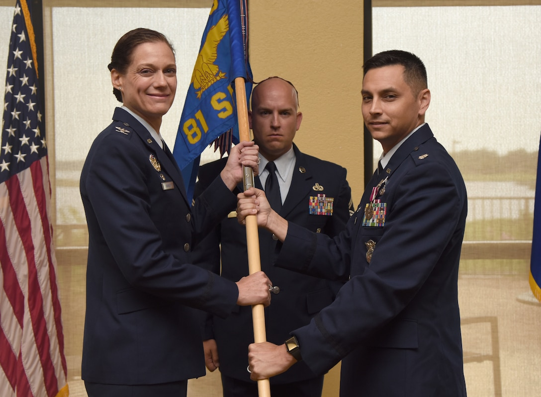U.S. Air Force Col. Marcia Quigley, 81st Mission Support Group commander, takes the 81st Security Forces Squadron guidon from Lt. Col. Jonathon Murray, outgoing 81st SFS commander, during the 81st SFS change of command ceremony inside the Bay Breeze Event Center at Keesler Air Force Base, Mississippi, May 31, 2019. The passing of the guidon is a ceremonial symbol of exchanging command from one commander to another. (U.S. Air Force photo by Kemberly Groue)