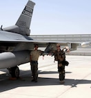 Two Airmen stand  under the wing of an F-16 Fighting Falcon fighter jet.