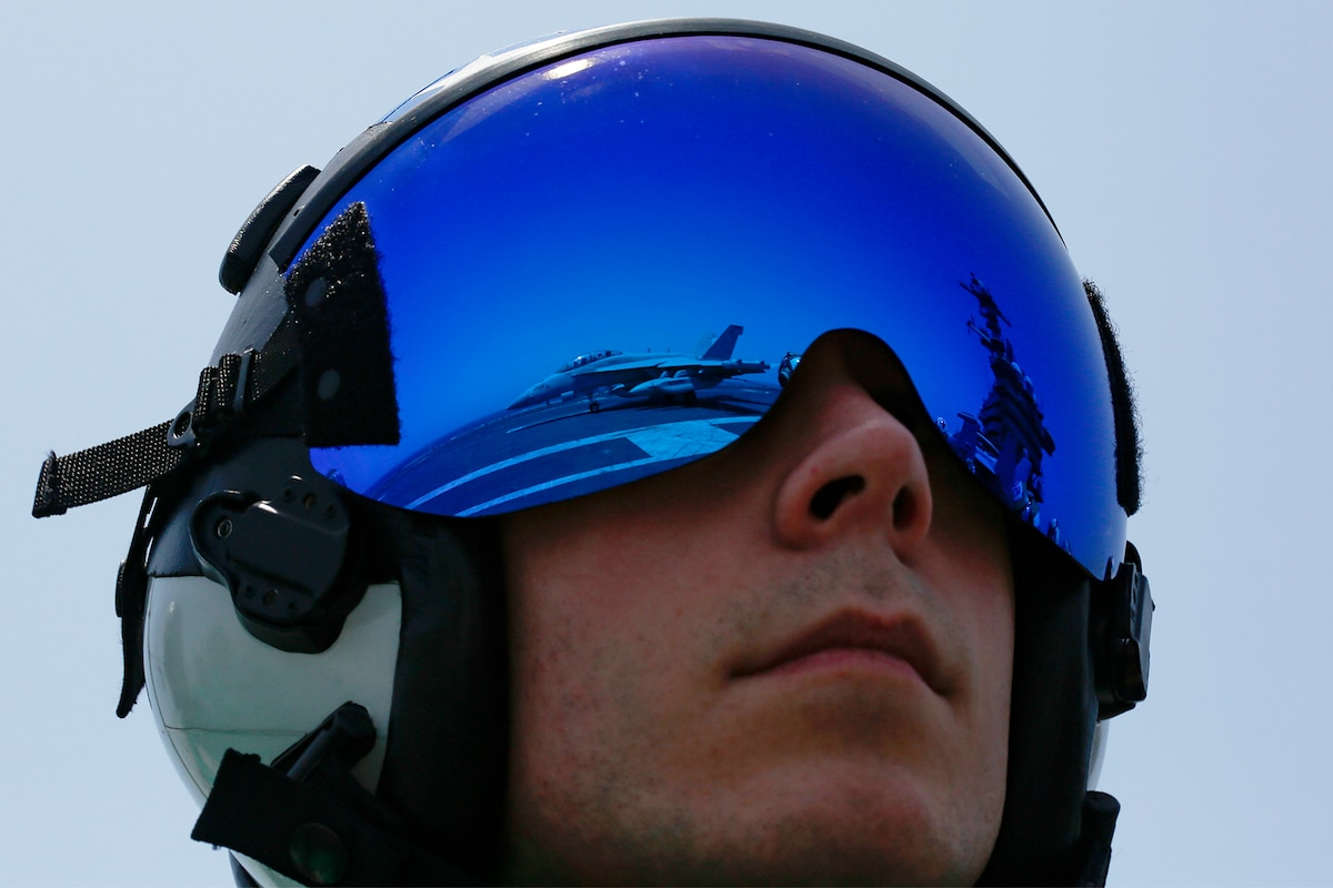 Aircraft are reflected on the blue helmet of a pilot.
