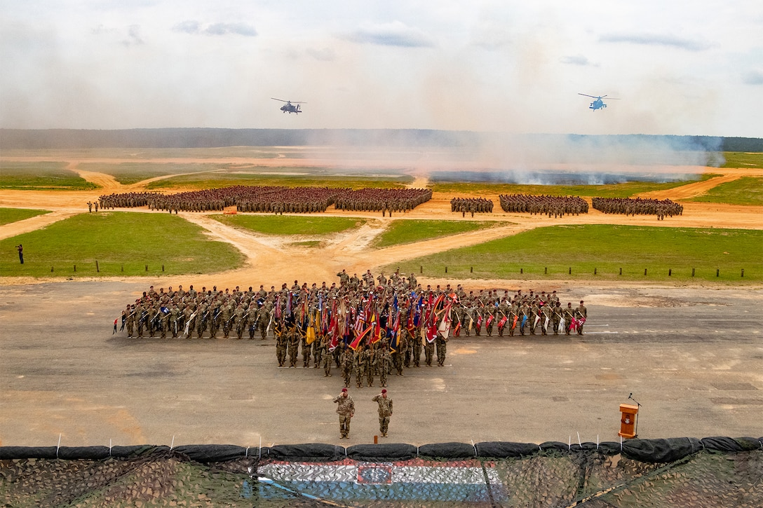 A large group of soldiers stand in formation on a field.