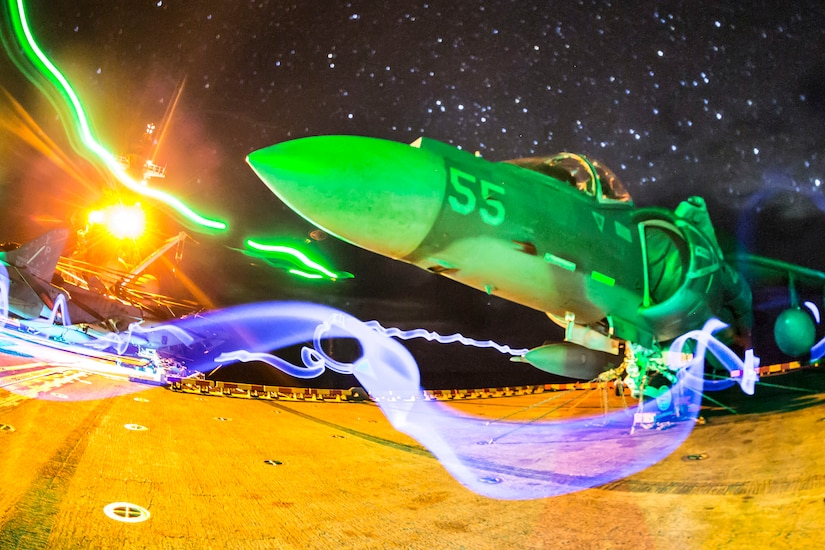 A Harrier jet sits on a ship bathed in colorful light.