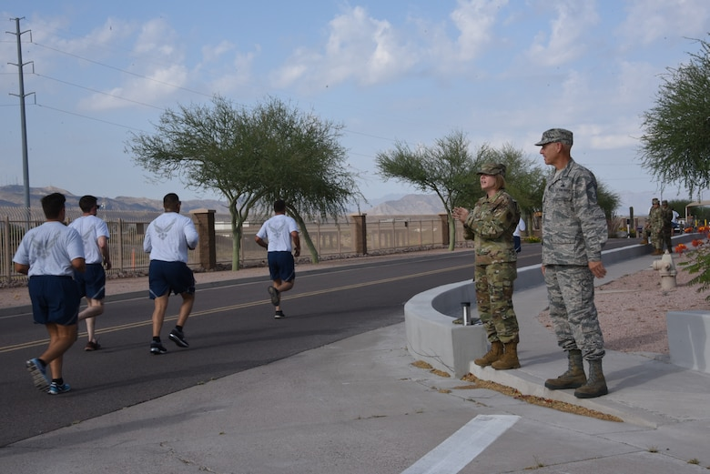 Chief Master Sgt. Rachel Landegent, 161st Air Refueling Wing mission support group superintendent, chants words of encouragement toward Airman while taking the running portion of their annual physical training assessment test June 2, 2019. Landegent enjoys inspiring Airman succeed. (U.S. Air National Guard photo by 1st Lt. Tinashe Machona)