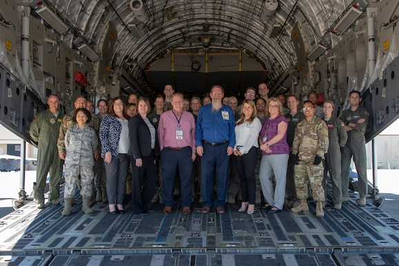 U.S. Air Force and civilian medical professionals pose for a photo on the aft loading ramp of a C-17 Globemaster III aircraft April 17, 2019, at Travis Air Force Base, California. Registered nurses from North Bay Healthcare Medical Center and the University of California Davis Medical Center spent the day touring several departments at David Grant USAF Medical Center and observed a patient transport demons