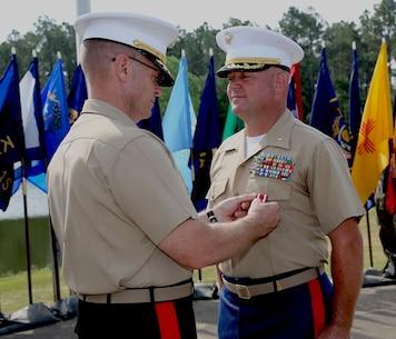 Maj. Will H. Anderson, right, deputy director, Supply Integration Division, Logistics Services Management Center, MARCORLOGCOM, receives the Meritorious Service Medal from Maj.Gen. Joseph F. Shrader, commanding general, MARCORLOGCOM, during a ceremony held at Covella Pond aboard MARCORLOGBASES Albany, GA., May 31. Anderson served over 30 years in the Marine Corps.